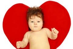 El bebé sorprendido contra corazón Fotografía de archivo libre de regalías