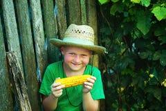 El bebé sostiene en sus manos un maíz hervido Fotografía de archivo libre de regalías