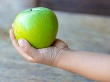El bebé sostiene una manzana verde en un fondo de madera, primer foto de archivo