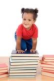 El bebé sube para arriba sobre una pila de libros Imagenes de archivo