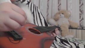 El bebé toca la guitarra con sus manos, y detrás del oso de peluche metrajes