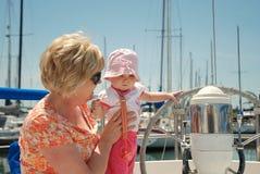 El bebé toca la rueda en un barco de vela Imágenes de archivo libres de regalías