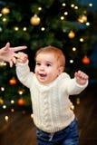El bebé toma las primeras medidas que llevan a cabo su mother& x27; mano de s en el fondo del árbol de navidad Fotos de archivo libres de regalías