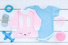 El bebé viste concepto El mono azul para el muchacho y la camisa rosada para la muchacha cerca de los accesorios del bebé en el f Fotos de archivo