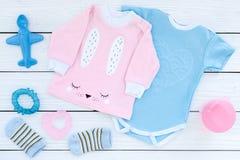 El bebé viste concepto El mono azul para el muchacho y la camisa rosada para la muchacha cerca de los accesorios del bebé en el f Fotografía de archivo libre de regalías
