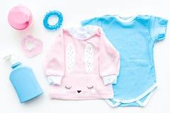 El bebé viste concepto Mono azul para el muchacho y la camisa rosada para la muchacha cerca de los accesorios del bebé en la opin Imagen de archivo