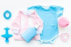 El bebé viste concepto Mono azul para el muchacho y la camisa rosada para la muchacha cerca de los accesorios del bebé en la opin Imagen de archivo libre de regalías