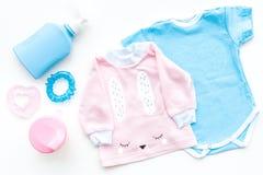 El bebé viste concepto Mono azul para el muchacho y la camisa rosada para la muchacha cerca de los accesorios del bebé en la opin Fotografía de archivo