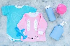 El bebé viste concepto Mono azul para el muchacho y la camisa rosada para la muchacha cerca de los accesorios del bebé en la opin Fotos de archivo libres de regalías