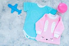 El bebé viste concepto Mono azul para el muchacho y la camisa rosada para la muchacha cerca de los accesorios del bebé en la opin Fotografía de archivo libre de regalías