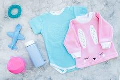 El bebé viste concepto Mono azul para el muchacho y la camisa rosada para la muchacha cerca de los accesorios del bebé en la opin Foto de archivo