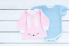 El bebé viste concepto Mono azul para el muchacho y la camisa rosada para la muchacha en el copyspace de madera blanco de la opin Foto de archivo libre de regalías