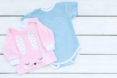 El bebé viste concepto Mono azul para el muchacho y la camisa rosada para la muchacha en el copyspace de madera blanco de la opin Foto de archivo