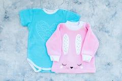 El bebé viste concepto Mono azul para el muchacho y la camisa rosada para la muchacha en la opinión superior del fondo gris Fotografía de archivo libre de regalías