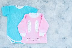 El bebé viste concepto El mono azul para el muchacho y la camisa rosada para la muchacha en la opinión superior del fondo gris co Fotografía de archivo libre de regalías
