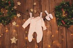 El bebé viste en la cuerda para tender la ropa en fondo adornado imagen de archivo