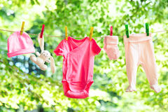 El bebé viste la ejecución en la cuerda para tender la ropa Imagen de archivo libre de regalías