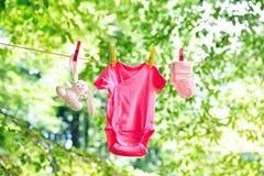 El bebé viste la ejecución en la cuerda para tender la ropa Fotografía de archivo