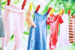 El bebé viste la ejecución en la cuerda para tender la ropa Foto de archivo libre de regalías