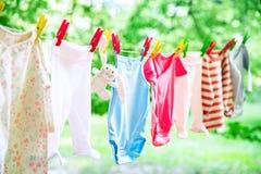 El bebé viste la ejecución en la cuerda para tender la ropa Imágenes de archivo libres de regalías