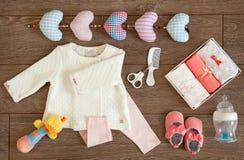 El bebé viste los accesorios y los juguetes coloridos en un arreglo tablero de la endecha del plano Fotografía de archivo libre de regalías