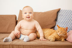 El bebé y el gato se sienta en el sofá, alergia infantil en felino fotos de archivo libres de regalías