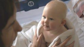 El bebé y la madre alegres se divierten en cama almacen de video