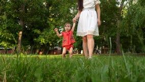 El bebé y la mamá están tomando sus primeras medidas que se sostienen sus entrega la hierba del césped en parque y la sonrisa de  metrajes
