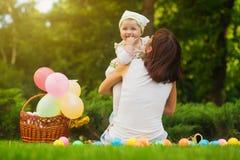 El bebé y la mamá lindos están jugando en la hierba verde Fotografía de archivo