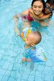 El bebé aprende nadar con la mama Fotos de archivo