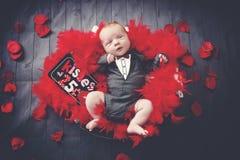 El bebé con la tarjeta del día de San Valentín besa la muestra Imagen de archivo libre de regalías