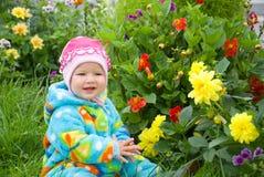 El bebé considera la flor Imagen de archivo