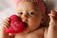 El bebé de la tarjeta del día de San Valentín come el corazón Imagen de archivo libre de regalías