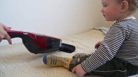 El beb? est? jugando con el aspirador hasta que la madre est? limpiando con la aspiradora almacen de video