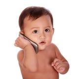 El bebé lindo hace una llamada de teléfono Imagen de archivo libre de regalías