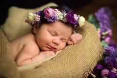El bebé recién nacido hermoso con una guirnalda púrpura duerme en una cesta de mimbre Fotografía de archivo