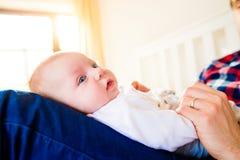 El bebé se sostuvo por su padre que se sentaba en cama Foto de archivo libre de regalías