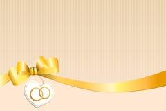 El beige abstracto del fondo pela el corazón amarillo blanco del arco con los anillos de oro de la boda Imagen de archivo