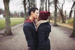 El besarse adolescente de los pares al aire libre en el parque Foto de archivo libre de regalías