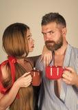 El besarse apasionado, muchacho y muchacha de los pares familia de hombre y de mujer con la taza roja de la leche imágenes de archivo libres de regalías