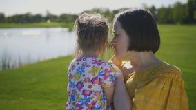 El besarse de la mamá y de la hija y sonrisa de abrazo metrajes