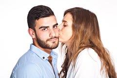 El besarse de los pares de la raza mixta aislado en el fondo blanco Imagen de archivo