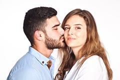 El besarse de los pares de la raza mixta aislado en el fondo blanco Imagenes de archivo