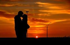 El besarse en la puesta del sol Fotografía de archivo