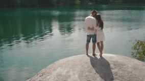 El besarse enloved hermoso de los pares al aire libre en a orillas del lago la colocación en roca grande almacen de video