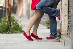 El besarse joven de los pares al aire libre Piernas masculinas y femeninas Fotografía de archivo