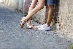 El besarse joven de los pares al aire libre Piernas masculinas y femeninas Imagenes de archivo