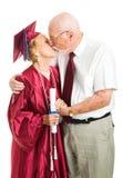 El besarse mayor de los pares de la graduación Fotografía de archivo libre de regalías