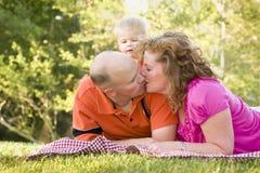 El beso cariñoso de los pares como hijo lindo mira encendido Fotos de archivo