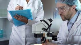El biólogo que estudia muestras debajo del microscopio, ayudante que anota comenta fotos de archivo